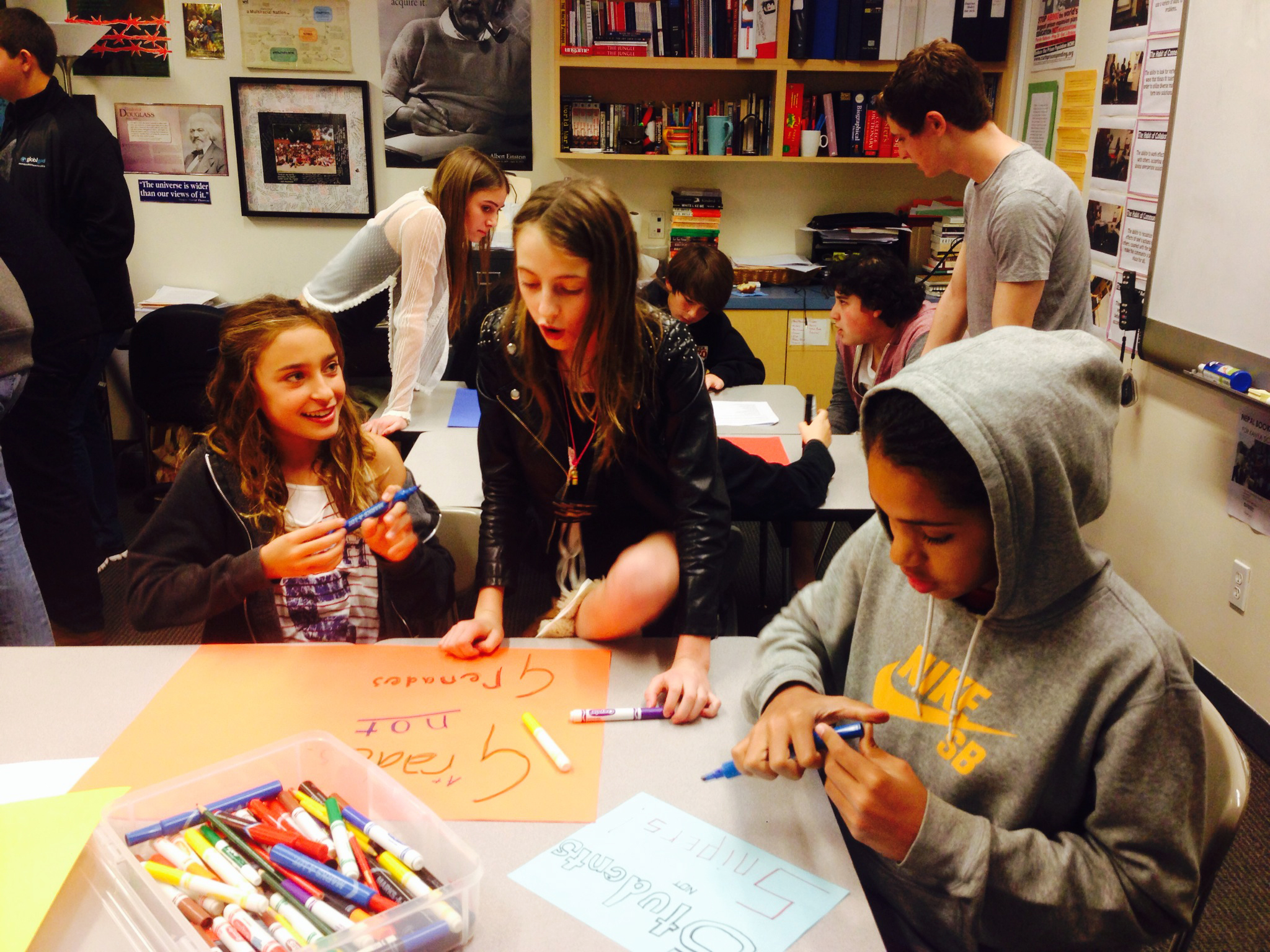 Middle school and high school students work together to create slogans for the Wildwood EMUS Campaign photo competition.