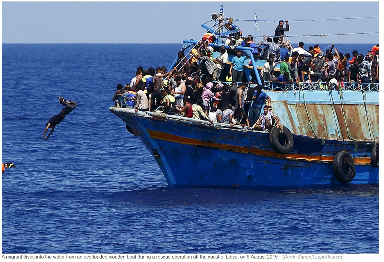 Migrant dives into the water from an overloaded wooden boat during a rescue operation off the coast of Libya on 6 August 2015