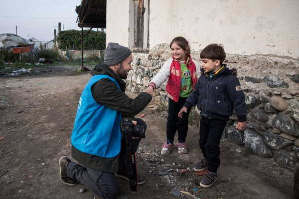 "Adam from UNHCR greets two refugee children waiting outside the transit camp in Gevgelija. UNHCR people work in three shifts for 7-10 days, followed by a two day break. ""I was interviewing a single mother travelling with two children from Syria, a boy and a girl. She was a very powerful person, always making sure her kids are still laughing. But at one moment, she started to cry. Her boy just quit playing what he was playing with and came to sit by his mother's side. He did not move until she stopped crying."" Photo by Al Jazeera."