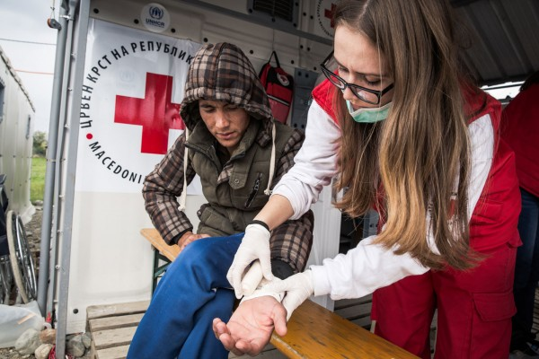"Ana, a Red Cross paramedic, dresses one refugee's bleeding wound. Red Cross team members work three days in the camp in 12-hour shifts, then they go home to Skopje for another three days. ""I am very impressed by their generosity. One day, a refugee boy came and donated some cough syrup for the other children. Other times, when we distributed hygiene kits, refugees were giving back the things they did not need to be used by others."" Photo by Al Jazeera."