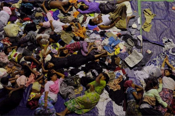 Exhausted after their ordeal at sea a group of rescued boat people sleep at a sports auditorium in Lhoksukon, in Aceh province, Indonesia. They have since been moved to another location in Kuala Langsa. Photo by UNHCR.