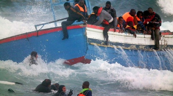 Refugees are rescued by Italian Coast Guard scuba divers, seen bottom left, in Pantelleria, Italy. Officials say two women drowned while attempting to reach Italy from North Africa after their boat with 250 people aboard went off course and ran aground just off an Italian island. Photo by Associated Press.