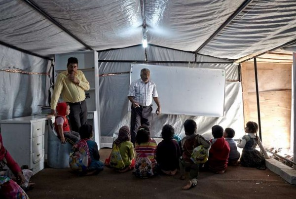 The school consists of a large tent, a whiteboard and a large rug the children sit on. There are no desks and the children keep their books on their laps. All of the students take classes together, regardless of age or grade level. Photo by UNHCR.
