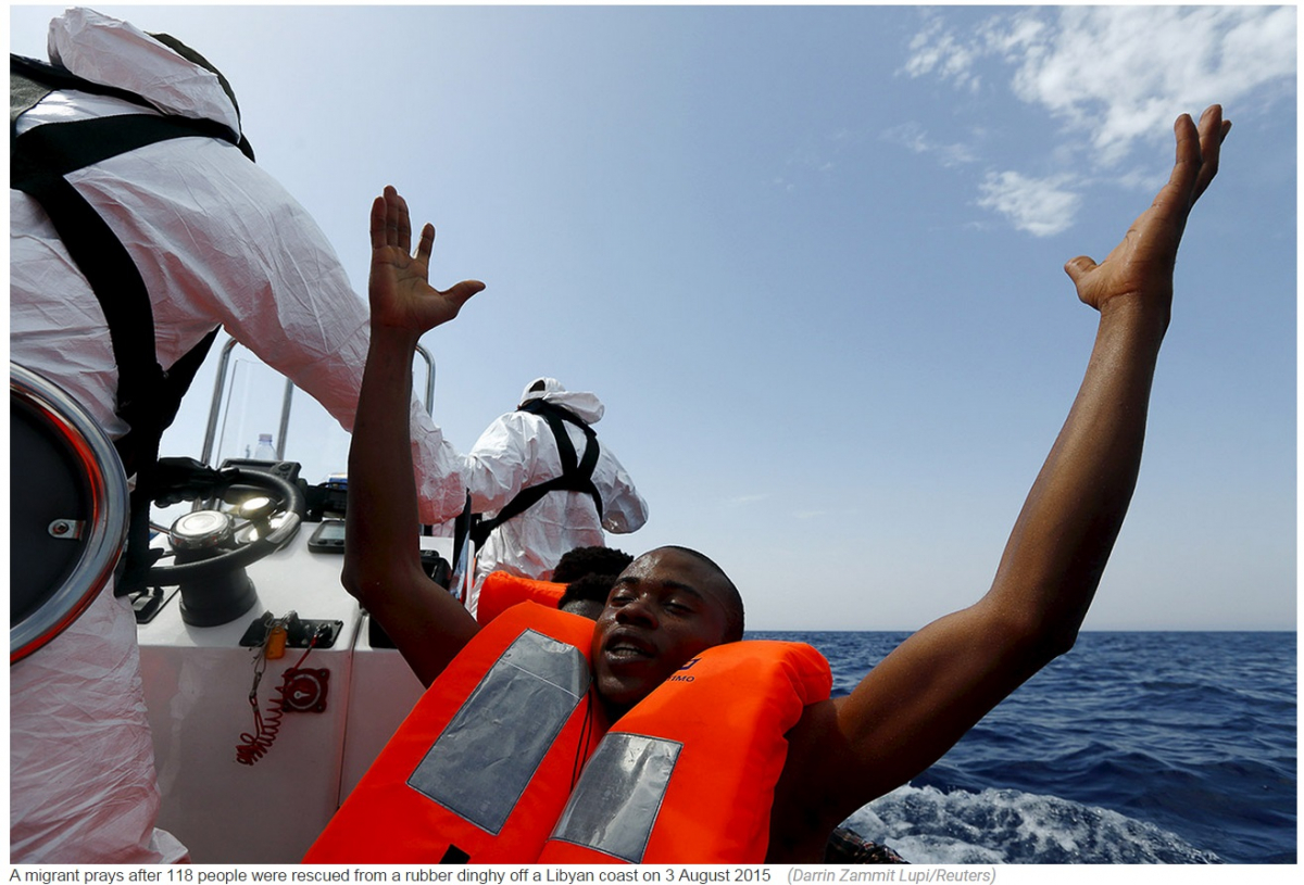 Migrant prays after 118 people were rescued from a rubber dinghy off a Libyan coast on 3 August 2015